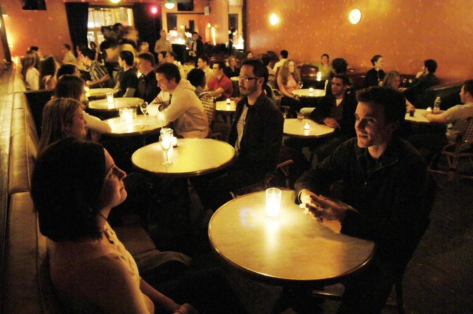 """New York, UNITED STATES:  Laura Julite (L-front) and Sam Janis (R, front) join other couples as they stare into each other's eyes by candlelight during an """"eyegazing"""" party, 16 January, 2006, in a Manhattan nightclub, part of the latest dating craze in New York City. Single people gather, sit in pairs and stare at each other for three minutes, then change partners. They do this for about one hour then gather for traditional cocktails.  AFP PHOTO/Stan HONDA  (Photo credit should read STAN HONDA/AFP/Getty Images)"""