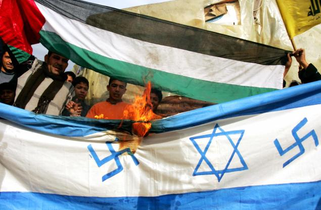 Palestinian protestors burn a makeshift Israeli flag, bearing Nazi swastikas on each side of the Star of David, during a demonstration against Israel's continuing assault on Gaza in the refugee camp of Ain el-Hilweh near the southern Lebanese port city of Sidon on December 30, 2008. Arab capitals have been the scene for daily protests since December 27 against the continuing Israeli onslaught in the Gaza Strip that has killed more than 360 Palesitnians. Israel today readied troops on the Gaza border and warned its assault on Hamas could last for weeks, as jets pummelled Islamist targets for a fourth day amid a diplomatic push for a truce. AFP PHOTO/MAHMOUD ZAYAT (Photo credit should read MAHMOUD ZAYAT/AFP/Getty Images)