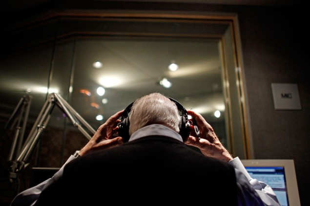 Long-time radio reporter Carl Kasell puts on headphones before delivering newscast (Photo: Chip Somodevilla/Getty Images).
