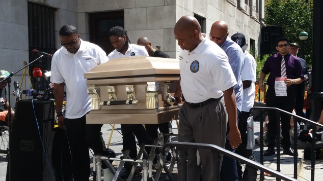 Brooklyn Borough President Eric Adams carries a casket outside Borough Hall today. (Photo: Ross Barkan/New York Observer.)