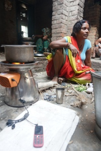 A woman charges her mobile while cooking. (Photo: Biolite)