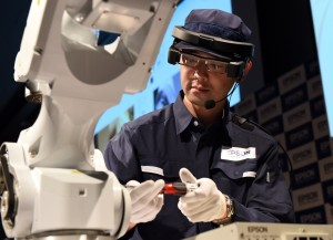 "A model demonstrates repairing an assembly line robot while wearing Epson's Moverio Pro BT-2000 business-use smart headset during a press preview in Tokyo on June 23, 2015. Epson will start the sale of the hands-free headset - which allows ""organizations to create and share applications"" in fields such as manufacturing, maintenance and education - from September this year to support manufacturing in the business field. AFP PHOTO / TOSHIFUMI KITAMURA"