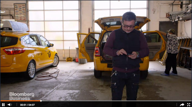 Borderline millennial Gene Freidman taps some sort of technological device in one of the many garages housing taxis he owns. (Bloomberg Business screencap)