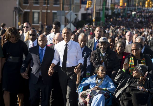 US President Barack Obama walks alongside Amelia Boynton Robinson (2nd-R), one of the original marchers, First Lady Michelle Obama (L), and US Representative John Lewis (2nd-L), Democrat of Georgia, and also one of the original marchers, across the Edmund Pettus Bridge to mark the 50th Anniversary of the Selma to Montgomery civil rights marches in Selma, Alabama, March 7, 2015. The event commemorates Bloody Sunday, when civil rights marchers attempting to walk to the Alabama capital of Montgomery to end voting discrimination against African Americans, clashed with police on the bridge. AFP PHOTO / SAUL LOEB (Photo credit should read SAUL LOEB/AFP/Getty Images)