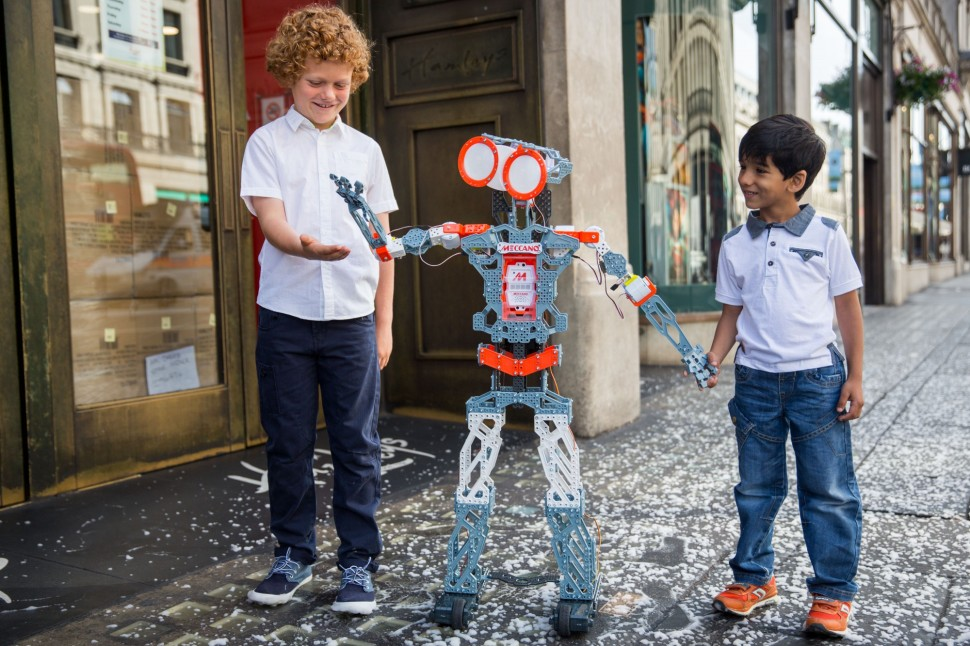 LONDON, ENGLAND - JUNE 25: Freddie, 9, and Miraan Jawed, 5, play with a 'Meccanoid G15 KS' robot outside Hamleys on Regent Street on June 25, 2015 in London, England. The robot, which is pre-programmed with over 1000 phrases and responds to voice commands, sells for £440. The Hamleys toy shop have made their predictions for the top selling toys for Christmas 2015. (Photo by Rob Stothard/Getty Images)