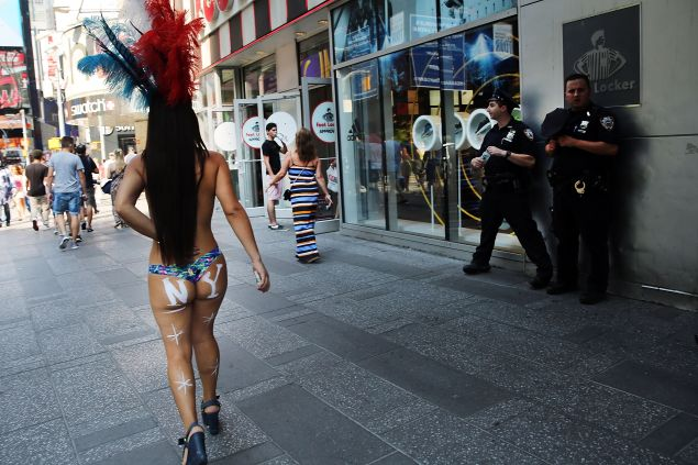NEW YORK, NY - AUGUST 18: (EDITOR'S NOTE: Image contains nudity) A semi-nude model walks in Times Square on August 18, 2015 in New York City. New York Mayor Bill de Blasio has announced that the city is preparing to address the issue of topless and painted women who pose for pictures in Times Square while soliciting tips. In recent years Times Square has seen an influx of performers who dress in a variety of costumes and sometimes become aggressive with the public. The semi-nude women, who call themselves desnudas, Spanish for naked, and pose for photos in exchange for tips, are a new addition to the colourful environment. (Photo by Spencer Platt/Getty Images)