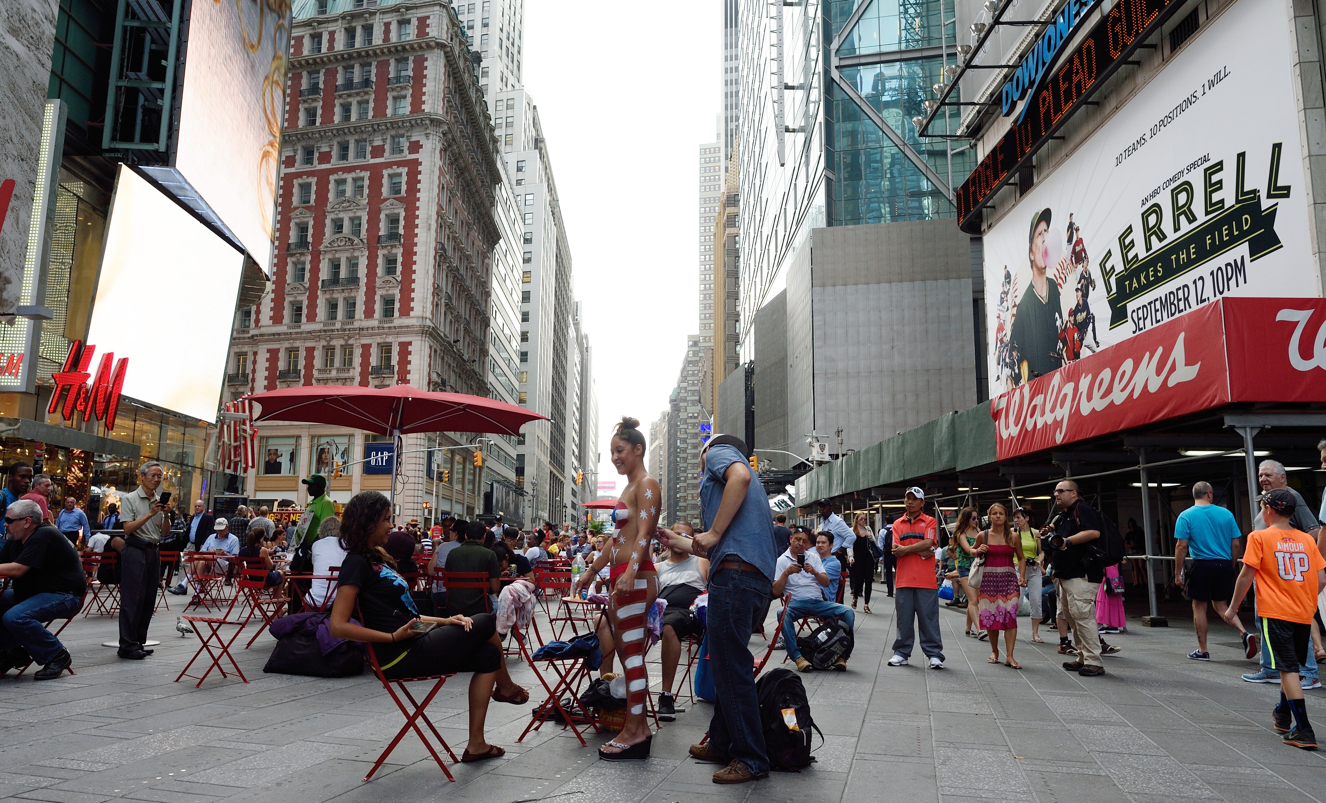 A young woman has her body painted in a Times Square pedestrian plaza. (Photo: DON EMMERT/AFP/Getty Images)