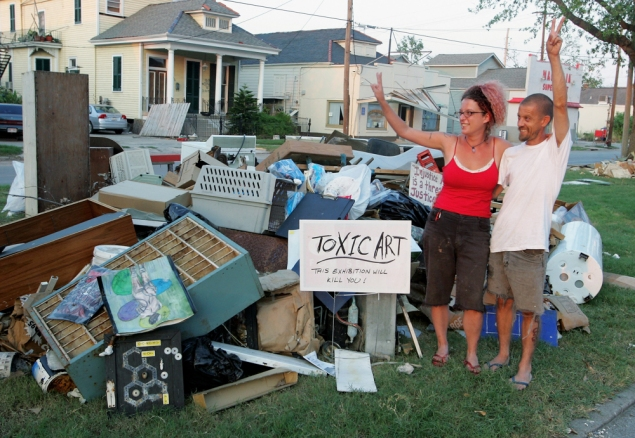 Artist Andrea Garland and her husband, artist Jeffrey Holmes, wave to passers-by as they pose by their display of damaged artwork in 2005. (Photo by Ethan Miller/Getty Images)