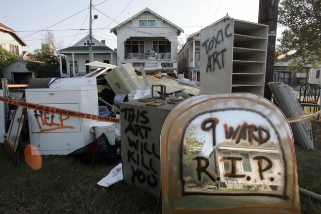 """More Toxic Art by Jeffery Holmes looks out from the balcony of his home (center in background) of a part of his """"toxic art"""" exhibition on the median of the roadway in front of his home in the Ninth Ward of New Orleans, 27 September 2005. The """"toxic art"""" consists of artworks from his home by himself and his wife, as well as everyday items from their home, all of which were ruined by the floodwaters from Hurricane Katrina. AFP PHOTO / Robyn Beck (Photo credit should read ROBYN BECK/AFP/Getty Images)"""