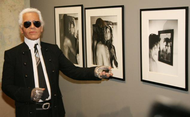 Mr. Lagerfeld poses with photos he took of Brad Kroenig. (Photo: OLIVER LANG/AFP/Getty Images)