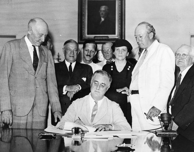 FDR signs Social Security legislation with Frances Perkins perched over his left shoulder.