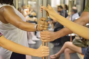 New Yorkers share a subway pole, despite a crowded car. (Photo by Richard Yeh/WNYC)