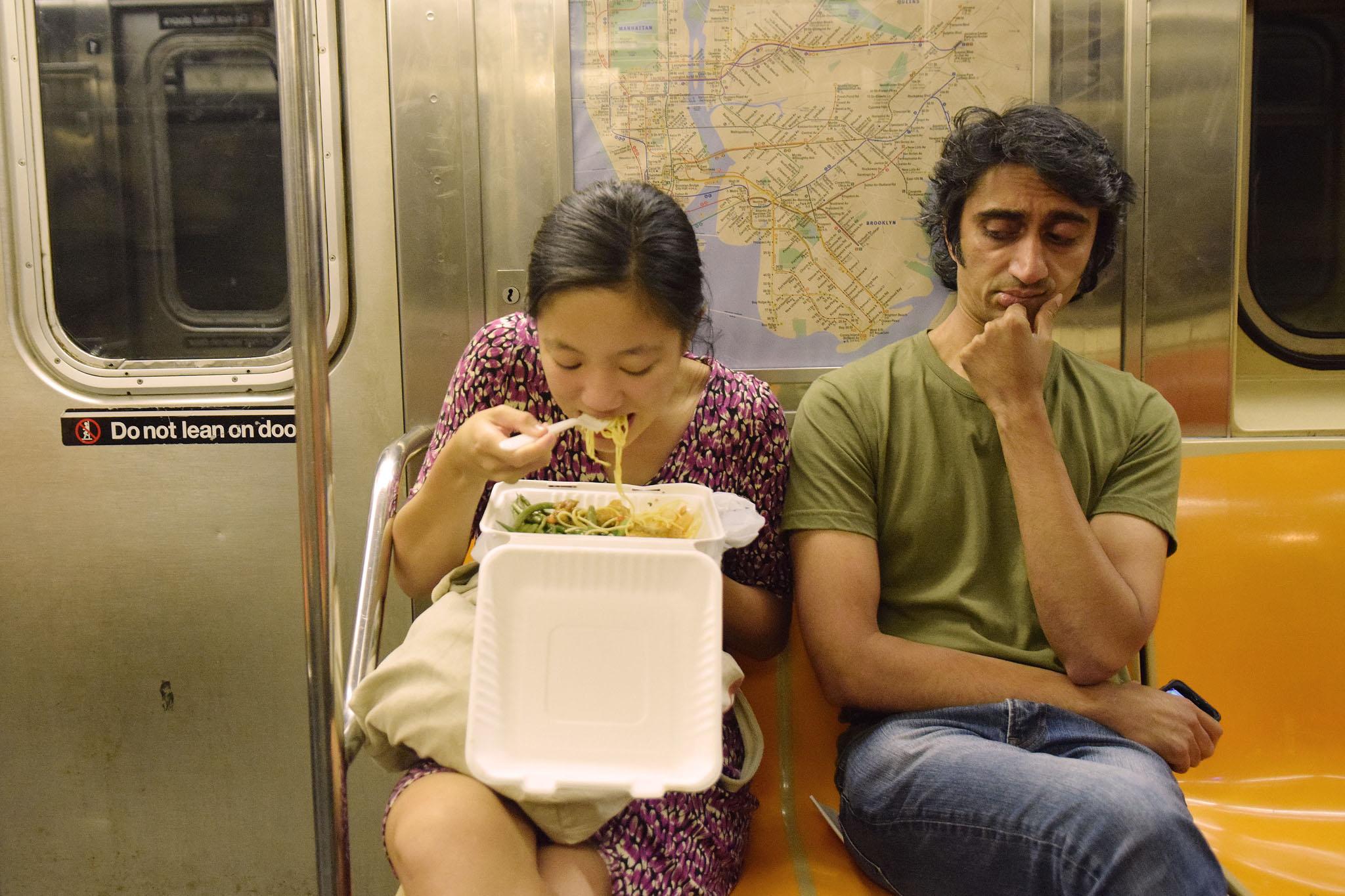 Eating takeout on the subway. (Photo: Richard Yeh / WNYC)