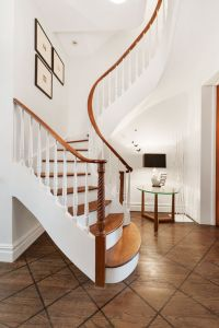 The curved wooden staircase leads up to three bedrooms. (Corcoran)
