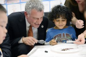 Mayor Bill de Blasio works with a student on a science project during a visit to a pre-K classroom in Manhattan. (GettyImages)