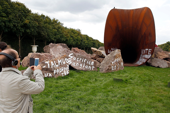 "A visitor takes a picture of ""Dirty Corner"" by artist Anish Kapoor, vandalized for the second time in the gardens of the Chateau de Versailles. (Photo by Chesnot/Getty Images)"