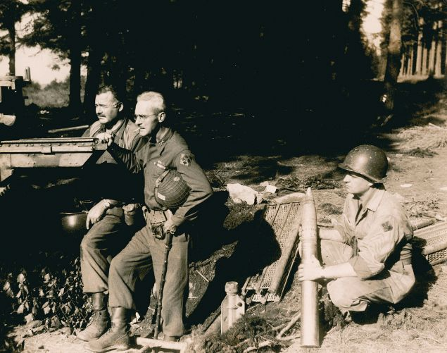 Hemingway, at left, beside Col. Charles 'Buck' Lanham in Germany during World War II. An unidentified soldier kneels to hold ammunition. (