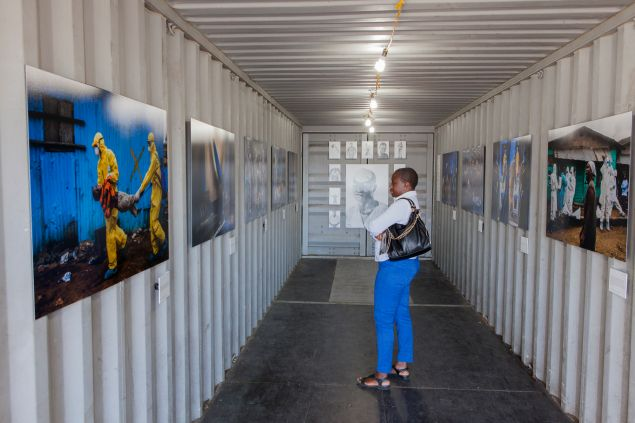 """A visitor looking at Daniel Berehulak's """"Scenes from the Ebola Crisis."""" (Photo: Alan Winslow)"""