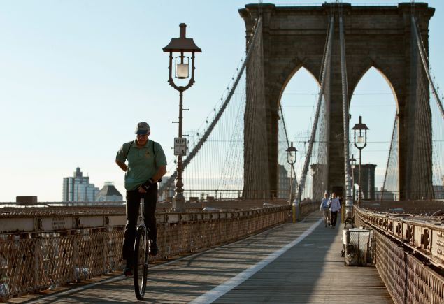 A man rides a unicycle across the Brooklyn Bridge into Manhattan. (Photo: Getty Images)