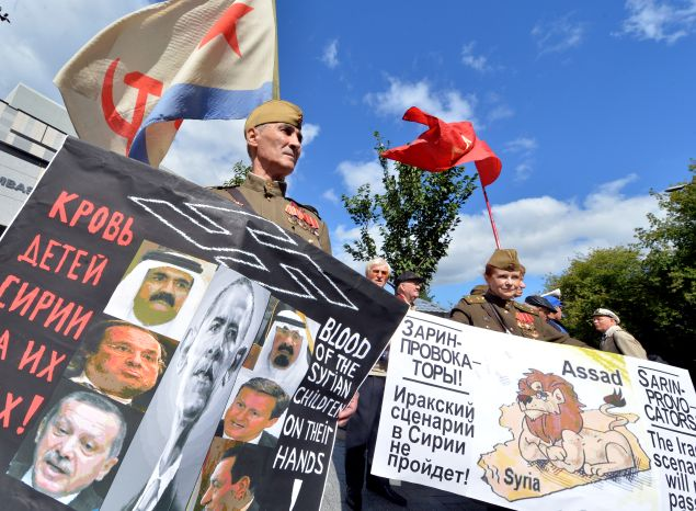 """A Soviet army veteran holds a placard depicting heads of state and reading """"Blood of Syrian children on their hands"""" during a protest outside the US embassy in Kiev on September 5, 2013. The rally organized by Ukrainian left-wing parties demanded a halt to a potential US attack against Syria. AFP PHOTO/ SERGEI SUPINSKY (Photo credit should read SERGEI SUPINSKY/AFP/Getty Images)"""