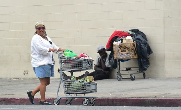 A homeless woman pushes her cart of belongings along a street in Los Angeles, California on August 25, 2015. According to a report released today by the Economic Roundtable, a nonprofit research group in Los Angeles, some 13,000 people tumble into homelessness every month in Los Angeles County, where the latest official count of the homeless found 44,000 people living along county streets during a three-day period in January, a increase of 12% in two years. AFP PHOTO /FREDERIC J.BROWN (Photo credit should read FREDERIC J. BROWN/AFP/Getty Images)