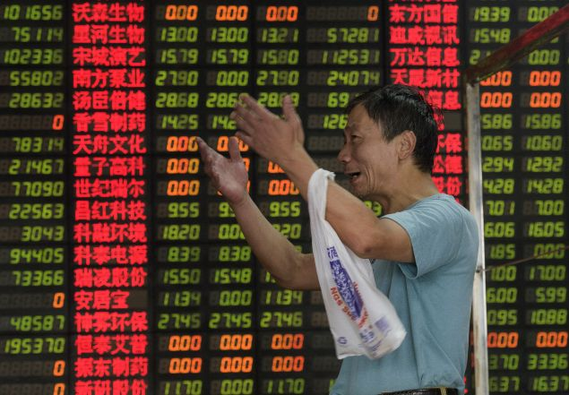 An investor in front of screens showing stock market movements at a Shanghai brokerage house. JOHANNES EISELE/AFP/Getty Images)