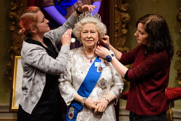 Stylists Jane Anderson and Luisa Compabassi pose with the re-styled wax figure of Britain's Queen Elizabeth II. (Photo: LEON NEAL/AFP/Getty Images)