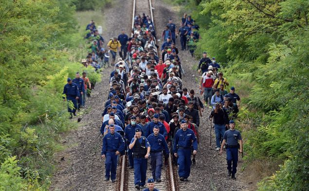 Refugees of different countries accompanied by police officers walk on the railway tracks near Szeged town as they broke out from the migrant collection point near Roszke village of the Hungarian-Serbian border on September 8, 2015. Hungary's border with Serbia has become a major crossing point into the European Union, with more than 160,000 entering Hungary so far this year including 2,706 on September 7, 2015 alone, police said. AFP PHOTO / ATTILA KISBENEDEK (Photo credit should read ATTILA KISBENEDEK/AFP/Getty Images)