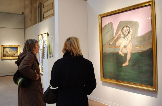 """Visitors look at Francis Bacon's """"Seated Woman"""" (Portrait of Muriel Belcher), 10 December 2007 at the Charpentier Galery in Paris. (Photo courtesy: Pierre Verdy/AFP/Getty Images)"""