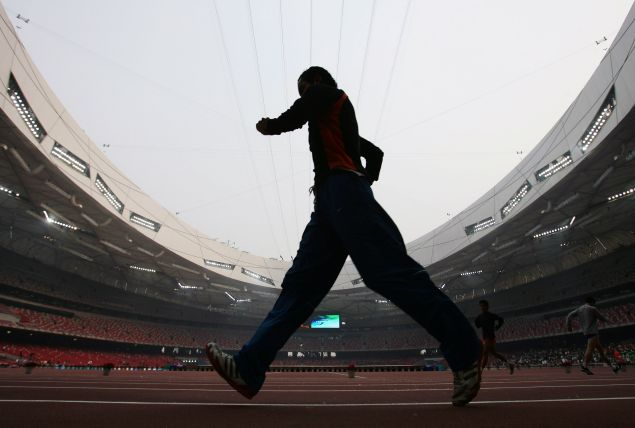 """BEIJING - APRIL 19:  Competitor warms up ahead the men's 50 km walk race during the 2008 BBMG IAAF Race Walking Challenge at the National Stadium, or the """"Bird's Nest"""", on April 19, 2008 in Beijing, China.  (Photo by Guang Niu/Getty Images)"""