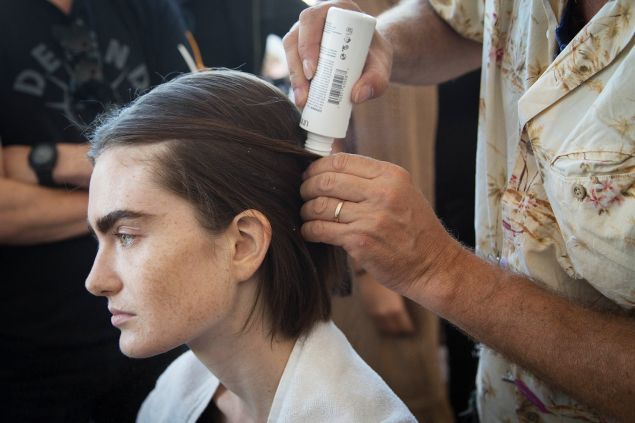 Mr. Ryan applies powder to a model's hair. (Photo: Observer/Kaitlyn Flannagan)