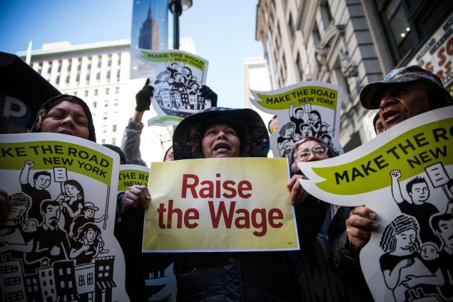 "NEW YORK, NY - MARCH 18: Women hold banners during a protest for higher wages for fast food workers on March 18, 2014 in New York City. The protest, arranged by the group ""Fast Food Forward"" accused fast food corporations of corporate greed and withholding wages. (Photo by Andrew Burton/Getty Images)"