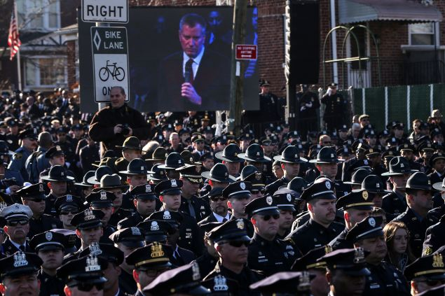 Law enforcement officers turn their backs on a live video monitor showing New York City Mayor Bill de Blasio as he speaks at the funeral of slain New York Police Department (NYPD) officer Rafael Ramos near Christ Tabernacle Church in the Queens borough of New York December 27, 2014. Tens of thousands of police and other mourners filled a New York City church and surrounding streets for the funeral on Saturday of one of two police officers ambushed by a gunman who said he was avenging the killing of unarmed black men by police. Singled out for their uniforms, the deaths of Rafael Ramos and his partner Wenjian Liu have become a rallying point for police and their supporters around the country, beleaguered by months of street rallies by protesters who say police practices are marked by racism. REUTERS/Shannon Stapleton (UNITED STATES - Tags: CIVIL UNREST POLITICS CRIME LAW TPX IMAGES OF THE DAY) - RTR4JDQZ