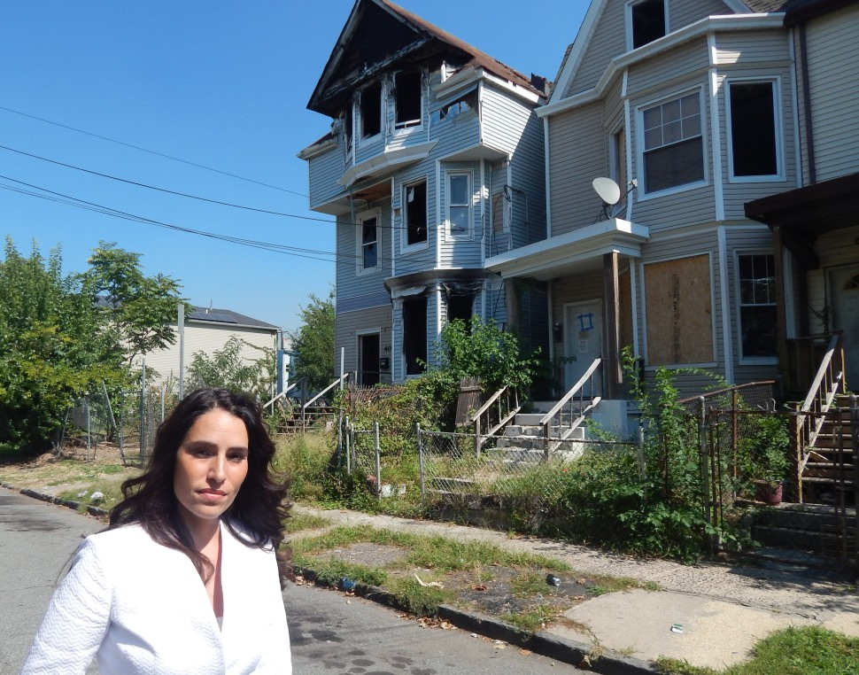 The sponsor a land banking bill targeting urban foreclosure, state Senator M. Teresa Ruiz (D-29) stands in front of abandoned properties right around the corner from an elementary school in the North ward.