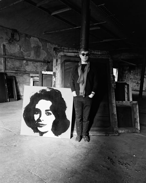 Evelyn Hofer, Andy Warhol standing in the Factory with a Liz painting and several screens in the background, January 29, 1964. (Photo: The Estate of Evelyn Hofer)