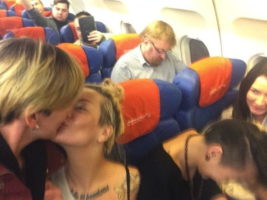 Lesbian activists who happened to be on a plane with anti-gay Russian lawmaker Vitaly Milonov arranged for him to photobomb them while kissing. (screencap CNN)