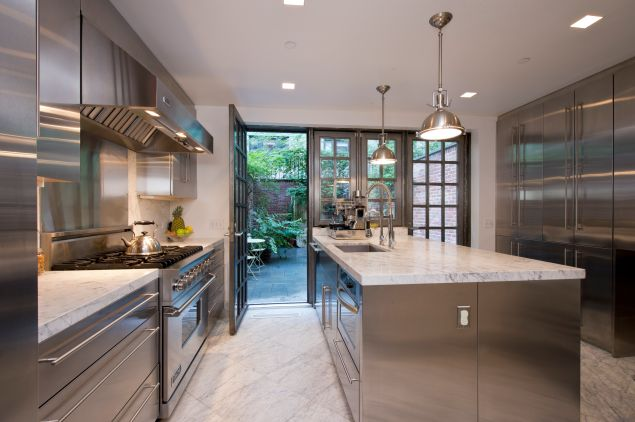 The Venturinos kitchen after the gut renovation, done in stainless steel and Carrera marble. (Juris Mardwig)