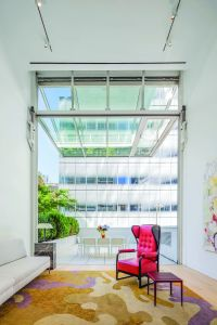 The all-glass wall opens up to reveal one of two private outdoor spaces in the unit. (The Corcoran Group)