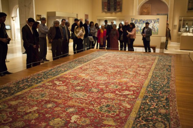 NEW YORK - DECEMBER 13: A guided tour group listens to a Metropolitan Museum of Art curator, 2nd right, December 13, 2011 as she explains one of the century's old Iranian carpets on view at the Nature of Islamic Art exhibit in New York City. The carpet, made in the 1550's, once decorated one of the residences of the Habsburg emperors. The Metropolitan Museum reopened and reinstalled the Islamic Art section in a 19,000 square foot wing after eight years of reconstruction. (Photo by Robert Nickelsberg/Getty Images)