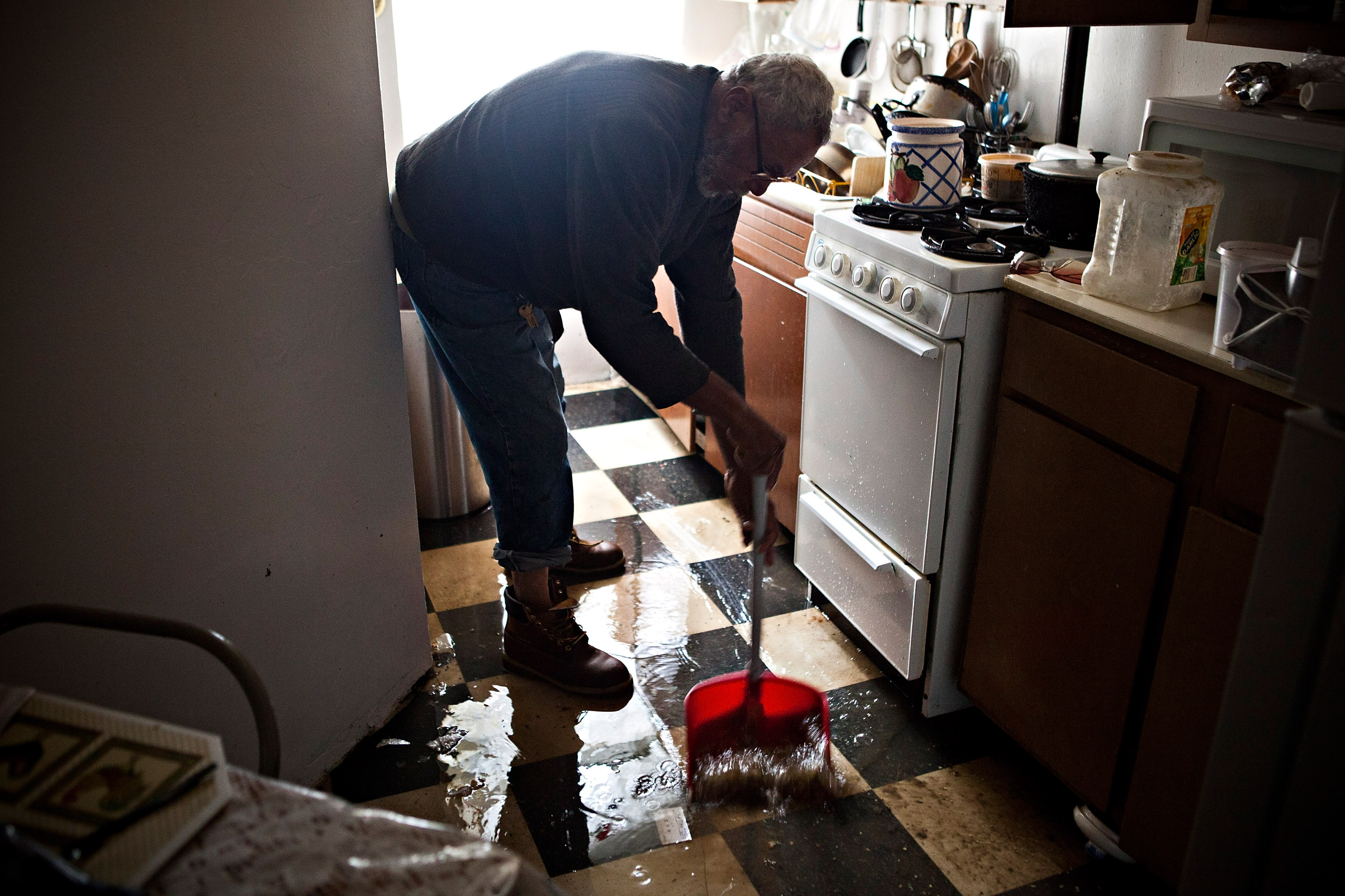 Jolito Ortiz helps sweep water out of his friend's apartment on the Lower East Side after Hurricane Sandy. (Photo by Andrew Burton/Getty Images)