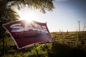 "POLK, NE - OCTOBER 11: A political sign for Ben Sasse, a Republican running for U.S. Senate who supports the proposed Keystone XL pipeline, is seen directly across the street from the ""Clean Energy Barn,"" which was built directly in the path of the proposed Keystone XL Pipeline and is equipped with solar panels and a wind turbine, on October 11, 2014 in Polk, Nebraska. The barn was built by Bold Nebraska, an organization opposed to the construction of the proposed pipeline. (Photo by Andrew Burton/Getty Images)"