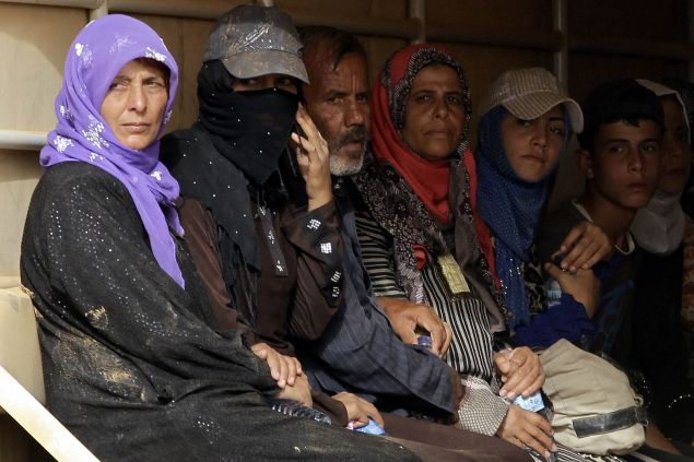Syrian refugees sit in the back of a Jordanian army truck. (Photo: AFP PHOTO / KHALIL MAZRAAWI (Photo credit should read KHALIL MAZRAAWI/AFP/Getty Images)