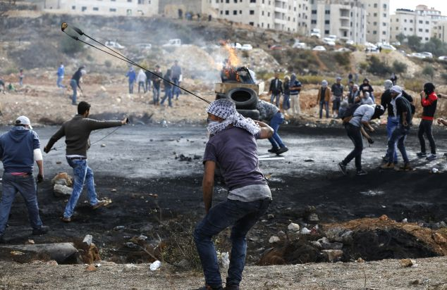 Palestinian protesters throw stones towards Israeli security orces during clashes at the northern entrance of the West Bank town of Al-Bireh, on the northern outskirts of Ramallah, in the West Bank, on October 27, 2015. Stabbings and violent protests have become daily occurrences since simmering tensions over the status of the Al-Aqsa mosque compound in Jerusalem's Old City boiled over in early October, leaving scores dead. AFP PHOTO / ABBAS MOMANI (Photo credit should read ABBAS MOMANI/AFP/Getty Images)