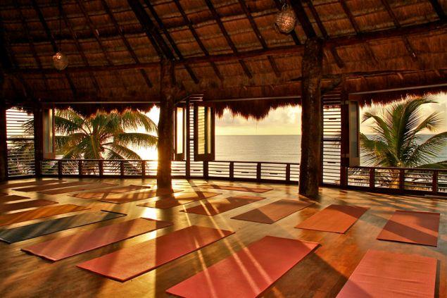 Beach front yoga won't have you overindulging on vacation (Photo: Amansala).