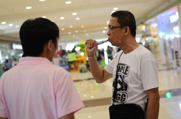 """MANILA, PHILIPPINES - JUNE 30: Consumers smoke electronic cigarettes at a mall on June 30, 2013 in Manila, Philippines. Electronic cigarettes are gaining popularity among former heavy smokers and are increasingly turning to the vapor-based slim metal tubes as an alternative to nicotine use. The use of E-cigarettes or """"Vaping"""", using a battery powered metal tube vaporizer to inhale nicotine infused with exotic flavors ranging from cinnamon to bubblegum have more than doubled in the past few years. Although not yet heavily regulated as tobacco, around a hundred stores catering to the rapidly expanding market have emerged. Philippine health officials have recently called for a temporary halt on the sale of electronic cigarettes pending further study and the unproven efficacy of the nicotine-based devices as well as being a dangerous gateway for minors to try smoking. (Photo by Dondi Tawatao/Getty Images)"""