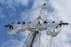 A crew unfurls the mast aboard Peacemaker.