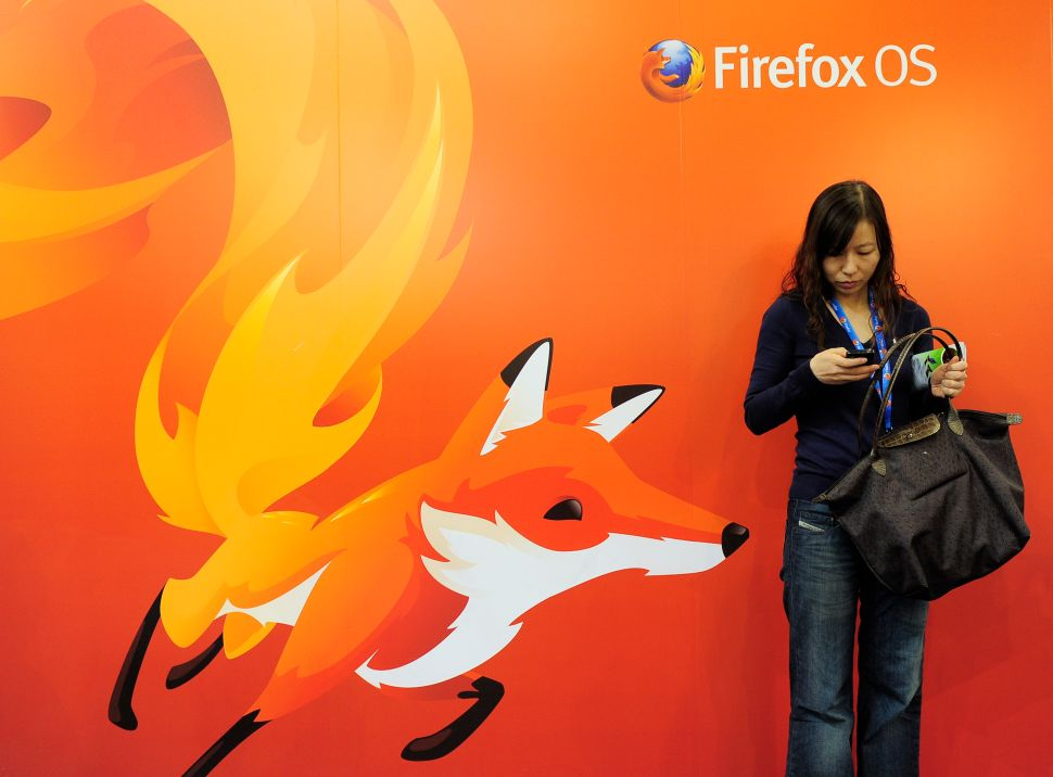 A woman looks at her mobile phone as she stands in front of a poster of Mozilla Firefox on February 27, 2013 at the Mobile World Congress, the world's biggest mobile fair, in Barcelona. The European Union warned member states on February 26 to free up the airwaves for new, super-fast fourth generation mobile networks and threatened legal action against those that deliberately block the process. AFP PHOTO/JOSEP LAGO