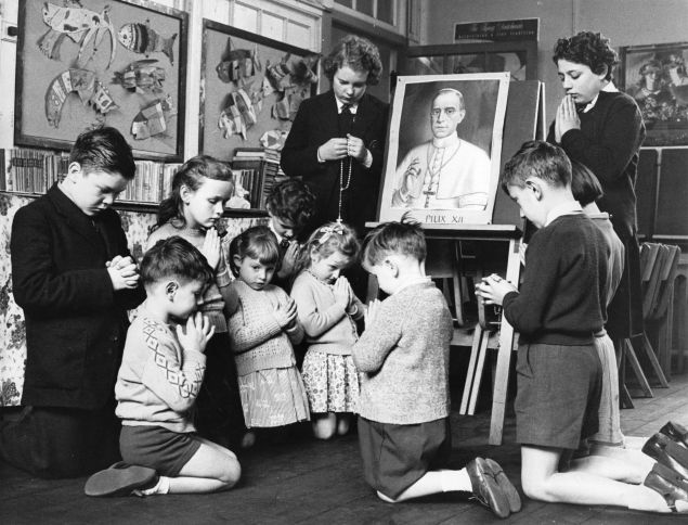 Pupils from the Italian Roman Catholic School in Clerkenwell, London, kneel before a picture of Pope Pius XII as his life hangs in the balance following a second stroke. (Photo by Reg Speller/Getty Images)