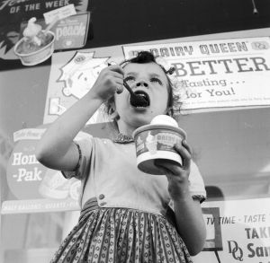 circa 1955: A young girl eating ice cream outside a Dairy Queen store. (Photo by Jacobsen /Three Lions/Getty Images)