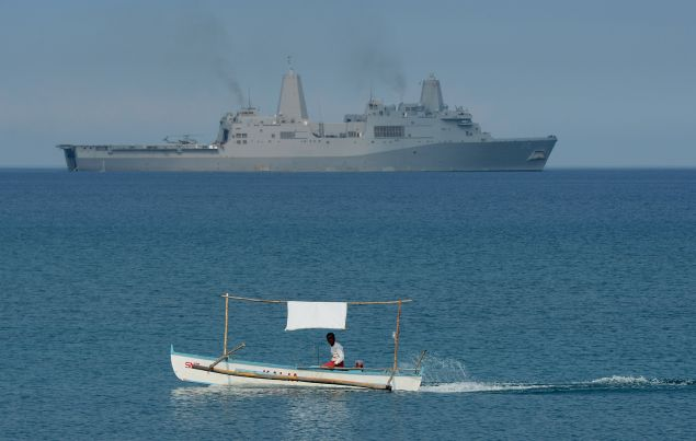 A Filipino fisherman passes a USS Green Bay during a landing exercise in the South China Sea. (Photo by TED ALJIBE/AFP/Getty Images)